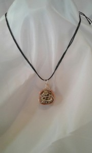 Firedog Pendant worn from a black cotton cord.