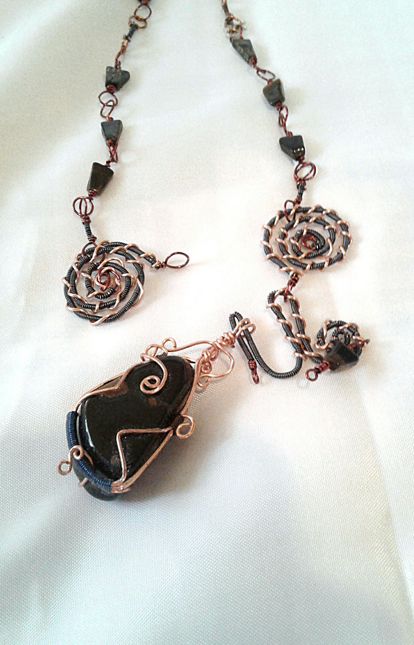 Sliding removeable pendant on opened clasp.
